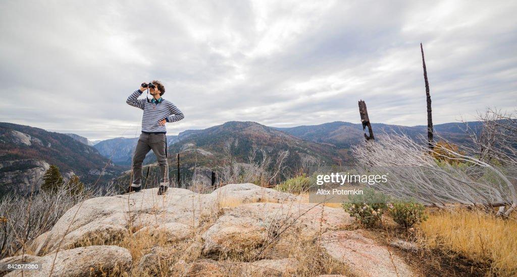 Jonge man, 25-jaar oude hipster, observeren van de natuur met de verrekijker uit de verhoogde rocky point in de buurt van in Devil dansvloer in het Yosemite Nationaal Park reizen : Stockfoto
