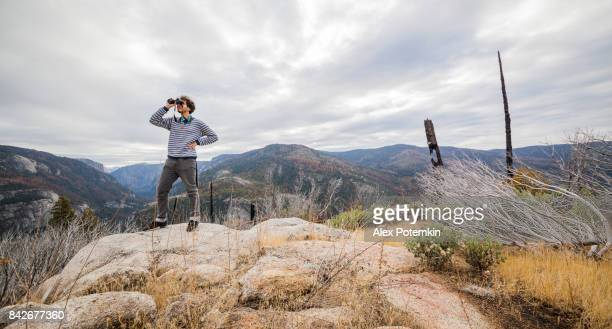 young man, 25-years-old traveling hipster, observing the nature with the binocular from the elevated rocky point near by devil dance floor in the yosemite national park - 25 29 years stock pictures, royalty-free photos & images