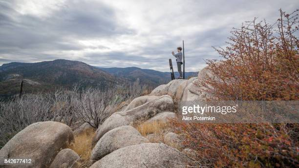 Young man, 25-years-old traveling hipster,filming with the action cam from the elevated rocky point near by Devil Dance Floor in the Yosemite National Park
