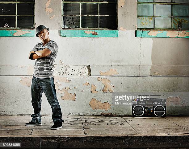 A young man, a breakdancer performer with a boombox on the street of a city.