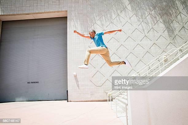 Young man, a parcour runner jumping in the air down a stairway.