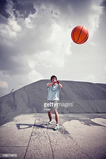 Junger Mann über, um Basketball