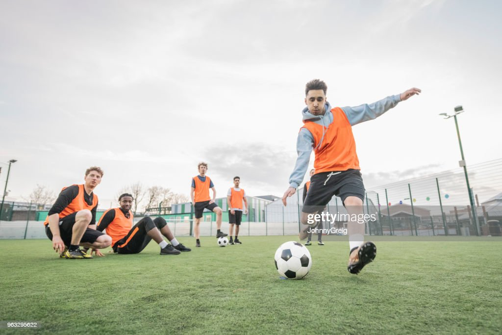 Young man about to kick football with team mates sitting on pitch and watching : Stock Photo