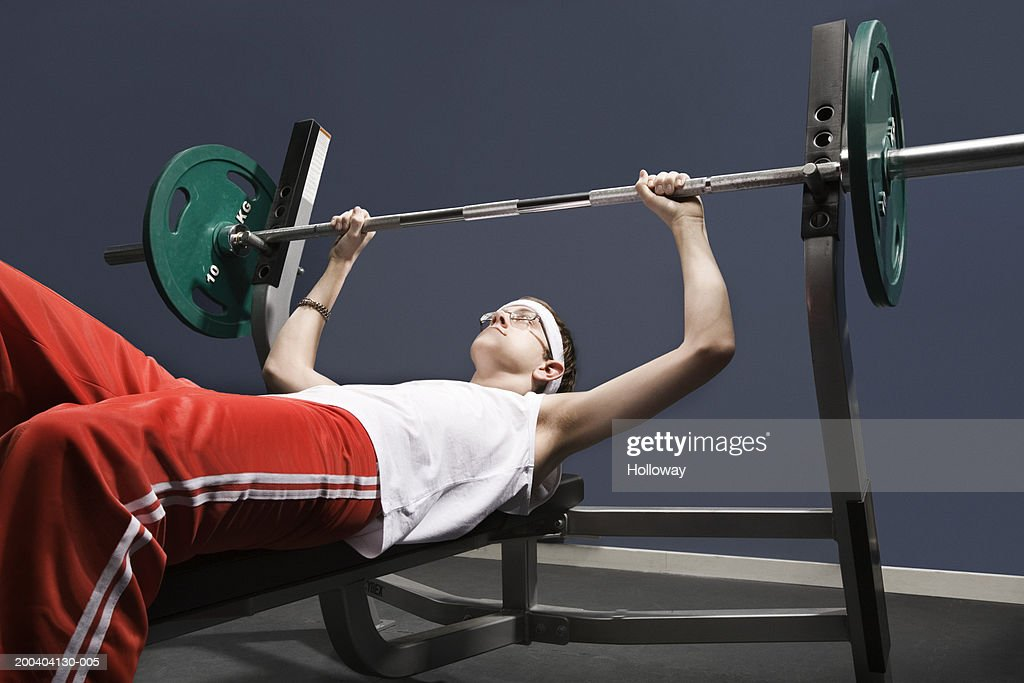 Young man about to lift weight in gym : Stock Photo