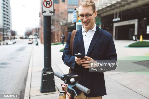 young man about to use a shared electric scooter - atlanta georgia stock pictures, royalty-free photos & images