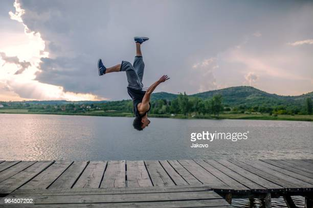 young man acrobat trains on a pier - cartwheel stock pictures, royalty-free photos & images