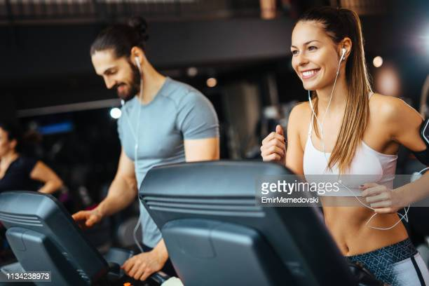 Young man adjusting speed on a treadmill at gym