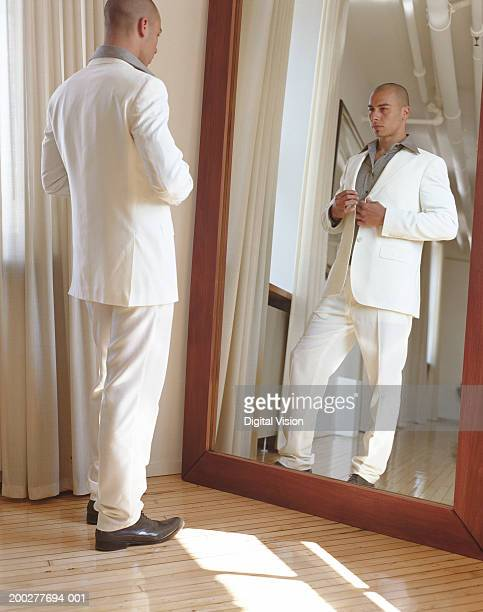 young man adjusting suit jacket in full length mirror - full length mirror stock photos and pictures