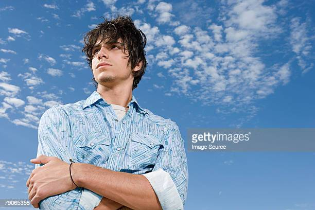 Young man against blue sky