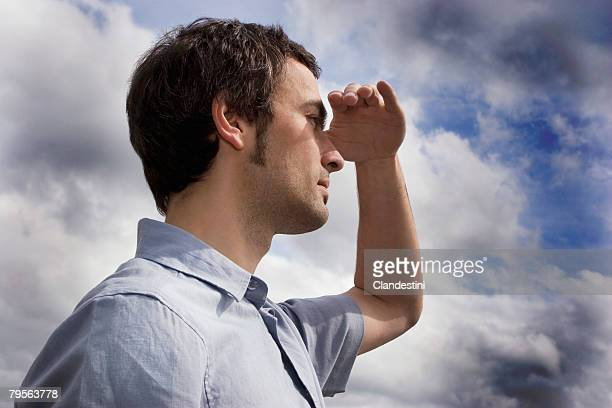 young man against cloudy sky, shielding eyes, side view, close-up - entfernt stock-fotos und bilder