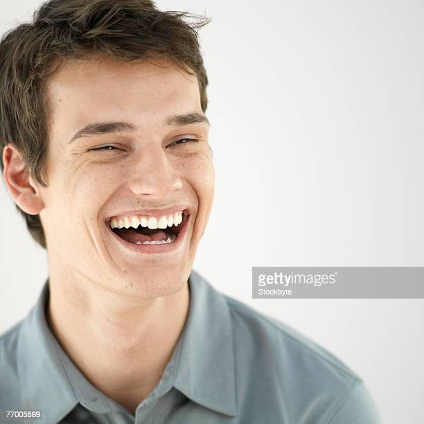 Young man against white background, laughing, head and shoulders