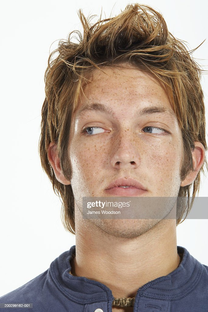 Young man against white background, looking to side, close-up : Stock Photo
