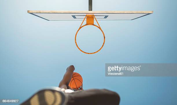 Young man aiming at basketball hoop