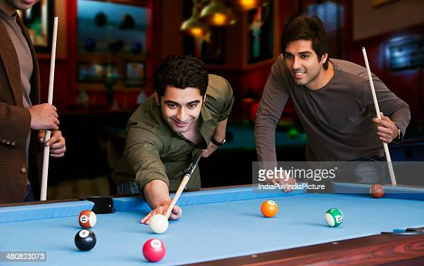 Young man aiming at cue ball while friends standing by pool table in club