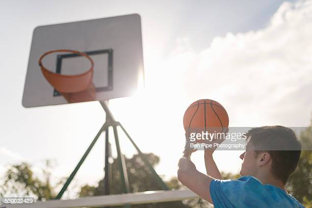 young man aiming to throw basketball into basketball hoop - bethnal green stock pictures, royalty-free photos & images