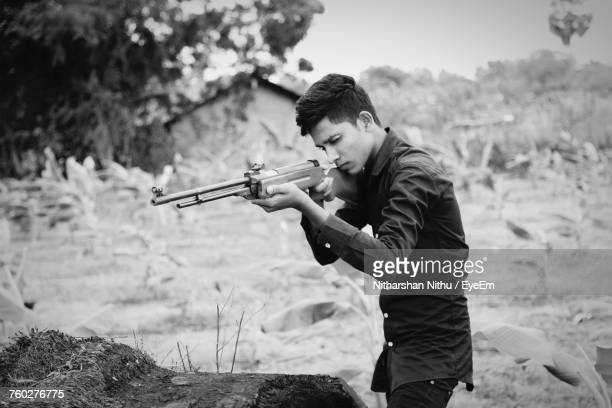 young man aiming with rifle while standing at farm - ライフル ストックフォトと画像