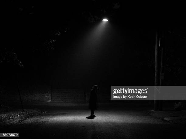 Young man alone under streetlight in vintage cloth