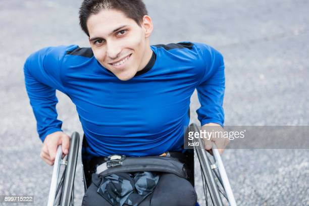 Young man, amputee in wheelchair, smiling at camera