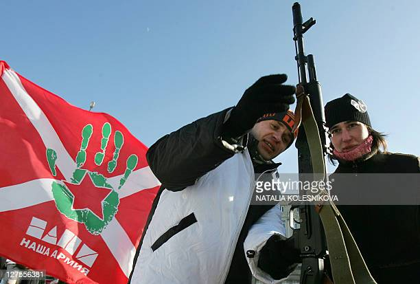 A young man and a girl hold a Kalashnikov submachine gun during a rally devoted to the national holiday celebrations the Day of the Fatherland's...