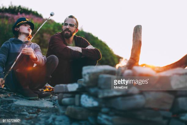 young man and a teenager enjoying a fire on the beach. vacations at the sea. father and son. eating marshmallow. sunset. gaspesie, quebec, canada - gaspe peninsula stock pictures, royalty-free photos & images