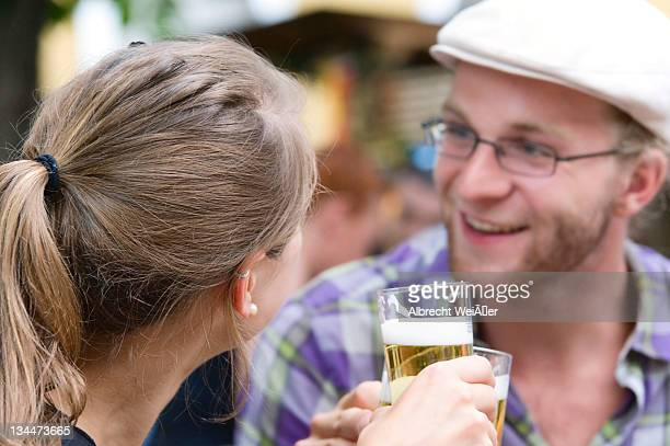 A young man and a young woman clinking beer glasses at a party, Germany, Europe