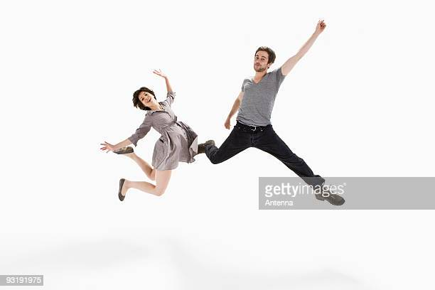 A young man and a young woman jumping mid-air