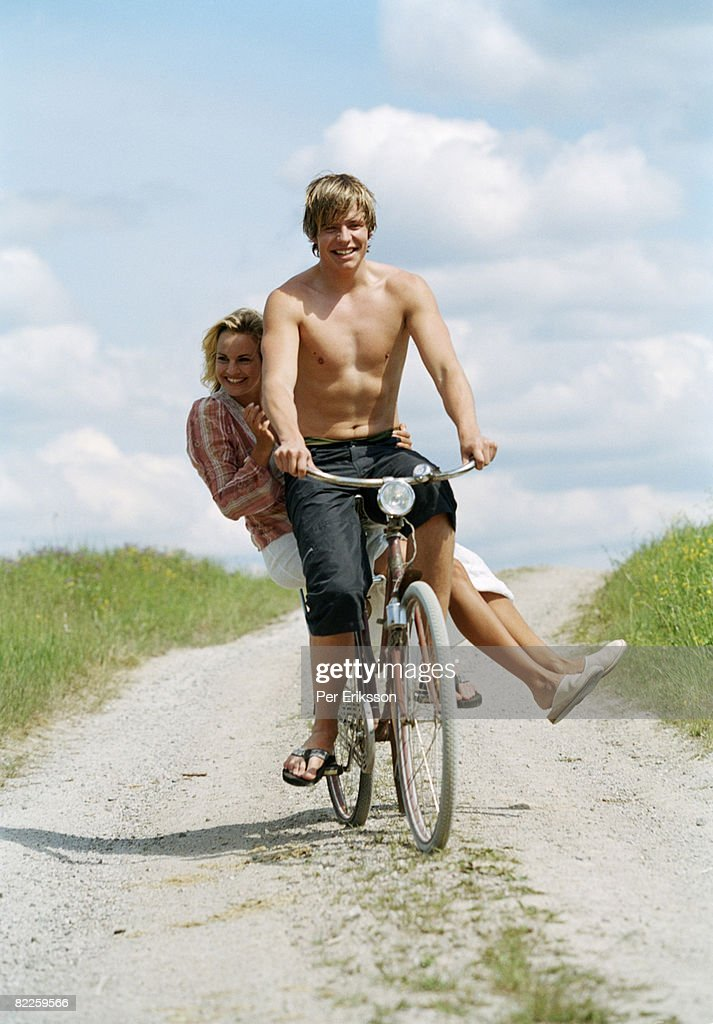 A young man and a young woman on a bike a sunny day Sweden. : Stock Photo