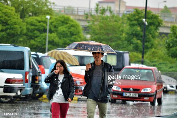 A young man and a young woman walk with an umbrella outside a shopping mall during heavy rainfall in the spring season in Ankara Turkey on Sunday May...