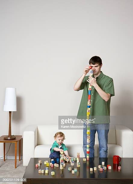 young man and baby boy (9-12 months) stacking blocks on coffee table - 12 23 months stock pictures, royalty-free photos & images