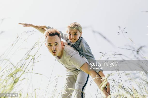 Young man and boy in a field pretending to fly
