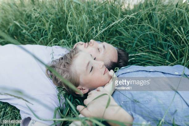 young man and boy lying in field - beschützer stock-fotos und bilder