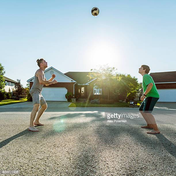 Young man and boy playing volleyball in neighborhood, Ontario, Canada