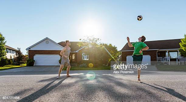 young man and boy playing volleyball in neighborhood, ontario, canada - alex potemkin or krakozawr stock pictures, royalty-free photos & images