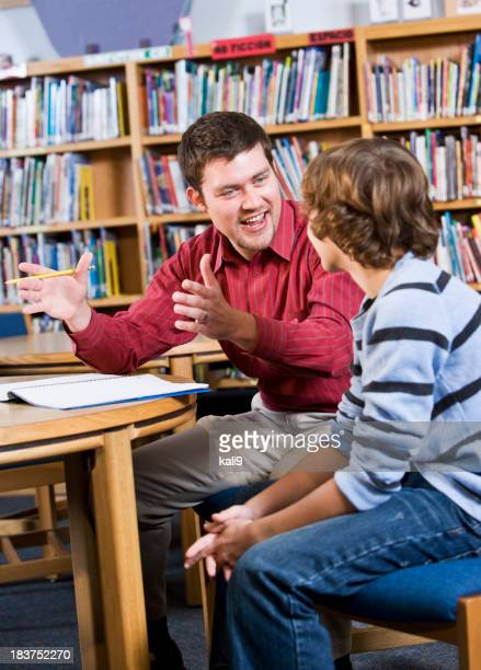 Young man and boy talking in school library
