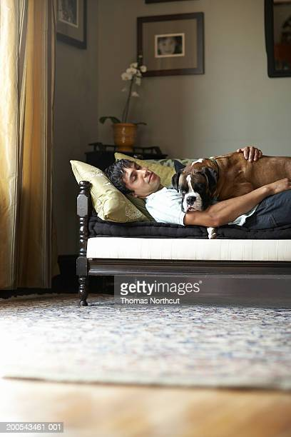 Young man and dog lying on sofa, side view