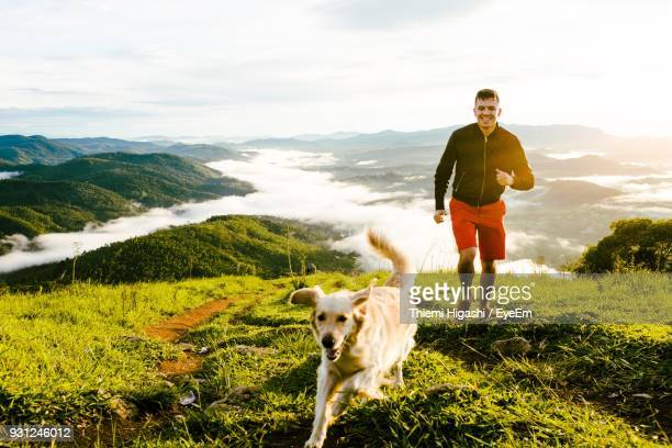 young man and dog running on mountain against cloudy sky - dog stock pictures, royalty-free photos & images