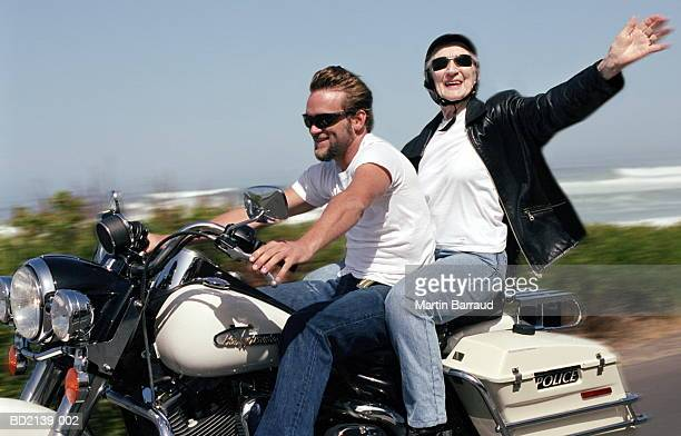 young man and elderly woman riding motorbike (blurred motion) - biker jacket stock photos and pictures