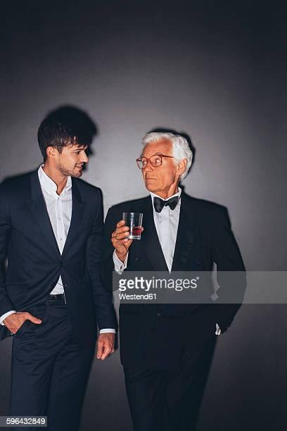 Young man and elegant senior man holding drink