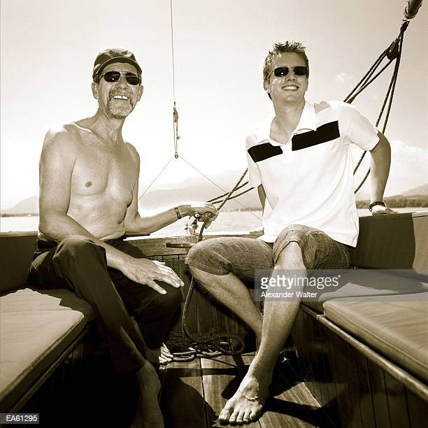 Young man and father at back of sailboat, wearing sunglasses (B&W)