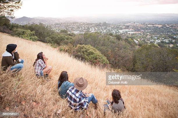 Young man and four adult sisters looking out from grassy hill