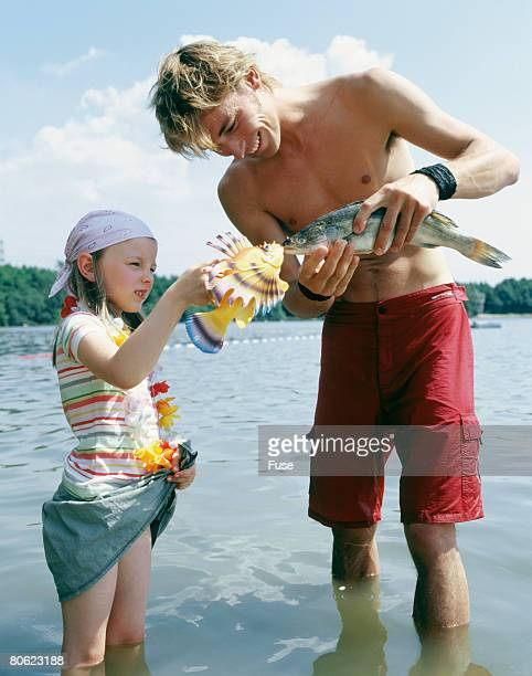 Young man and girl standing in water holding fish and plastic fish