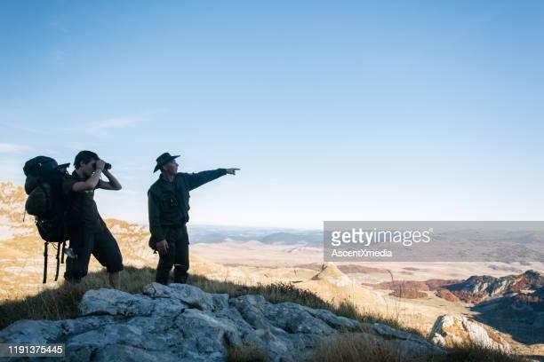 若い男とガイドは、山の双眼鏡を使用します - ツアーガイド ストックフォトと画像