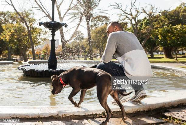 Young man and his dog at a fountain in the park.