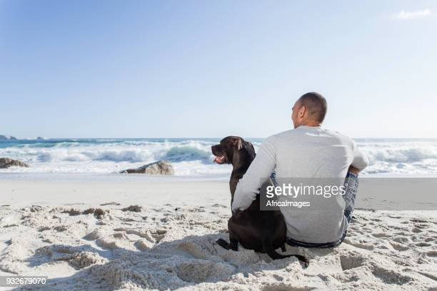 Young man and his dog sitting together on the beach.