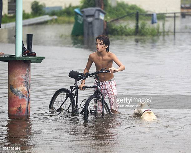 A young man and his dog wades in the storm surge from Hurricane Hermaine outside Cooter Stew Cafe on September 1 2016 in Saint Marks Florida...