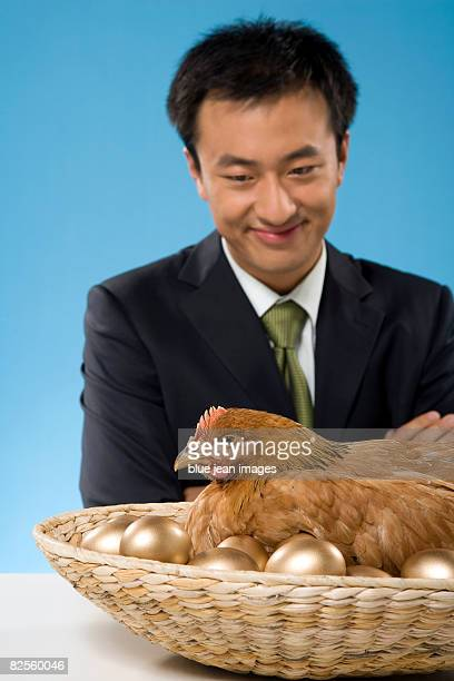 A young man and his golden egg laying hen.