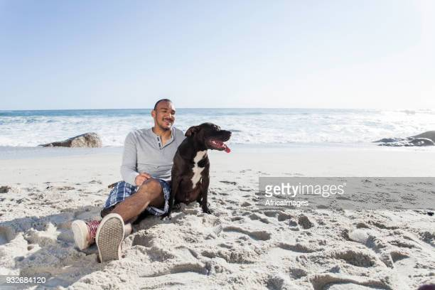 Young man and his pit bull sitting together on the beach.