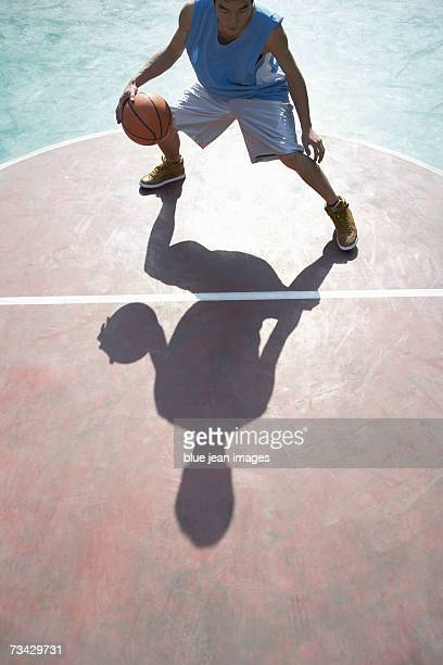 Young man and his shadow as he dribbles a basketball on an outdoor court.