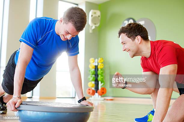 Young man and personal trainer with balance board.