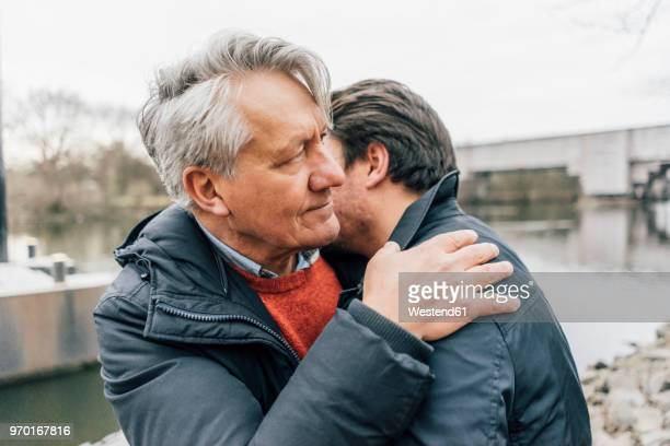 young man and senior man embracing at the riverside - trauer stock-fotos und bilder